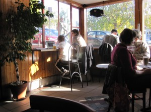 coffee shop hangers-on: kid on laptop; man with hand drawn peace-love shirt